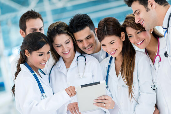 Group of doctors using health app on a tablet computer-min