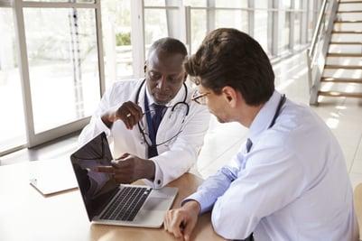 two-senior-healthcare-workers-in-consultation-PC8PKAJ-min