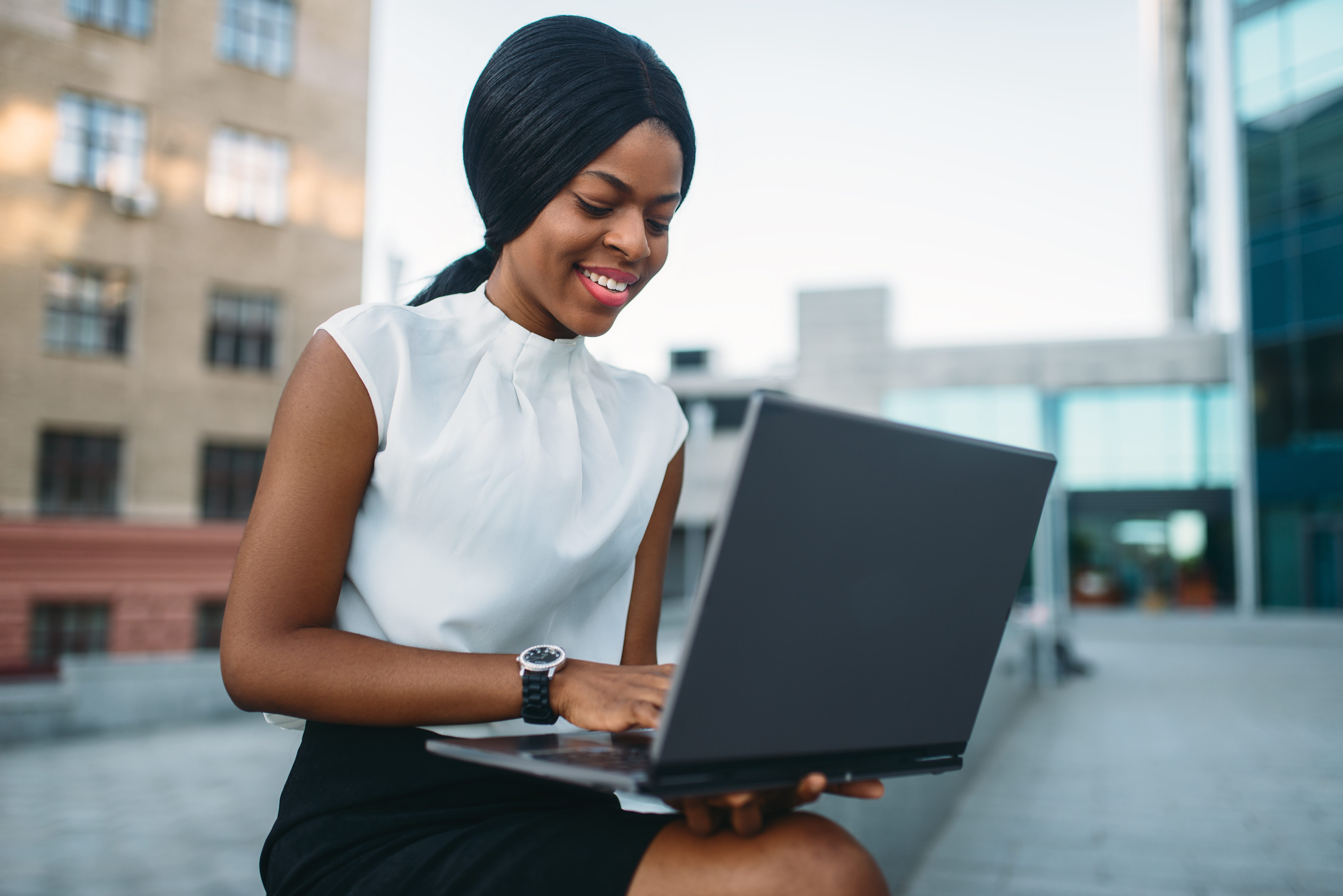 business-woman-uses-laptop-against-office-TUWGLHR